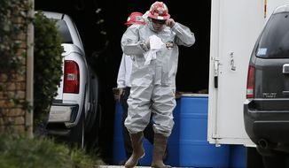 A Protect Environmental worker wears a hazard suite in a staging area at a healthcare workers apartment, who tested positive for Ebola, Oct. 13, 2014, in Dallas. (AP Photo/Brandon Wade)