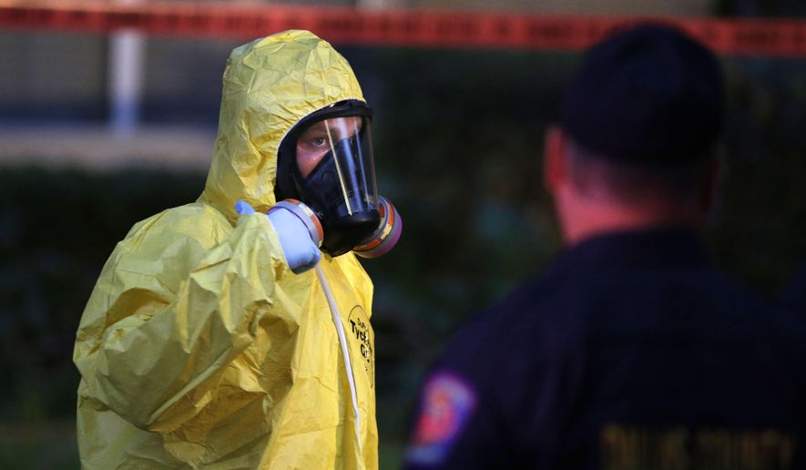 A hazmat worker looks up while finishing up cleaning outside an apartment building of a hospital worker, Sunday, Oct. 12, 2014, in Dallas. The Texas health care worker, who was in full protective gear when they provided hospital care for Ebola patient Thomas Eric Duncan, who later died, has tested positive for the virus and is in stable condition, health officials said Sunday. (AP Photo/LM Otero)
