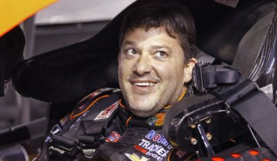 Tony Stewart smiles as he sits in his car before qualifying for Saturday's NASCAR Bank of America Sprint Cup series auto race at Charlotte Motor Speedway in Concord, N.C., Thursday, Oct. 9, 2014. (AP Photo/Terry Renna)