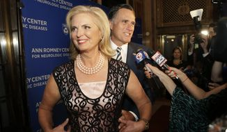 Ann Romney, left, and her husband Mitt Romney, center, walk past members of the media as they arrive at the Citi Performing Arts Center Wang Theatre before an event held to announce the Ann Romney Center for Neurologic Diseases, Tuesday, Oct. 14, 2014, in Boston. (AP Photo/Steven Senne) ** FILE **