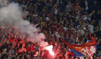 Serbian soccer fans react during the Euro 2016 Group I qualifying match between Serbia and Albania, at the Partizan stadium in Belgrade, Serbia, Tuesday, Oct. 14, 2014. The 2016 European Championship qualifier between Serbia and Albania was abandoned on Tuesday after skirmishes broke out on the pitch involving players and fans over an Albanian flag that was flown above the stadium by a drone. (AP Photo/Darko Vojinovic)