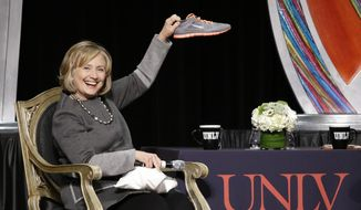 Former U.S. Secretary of State Hillary Rodham Clinton holds up a shoe during the UNLV Foundation annual dinner Monday, Oct. 13, 2014, in Las Vegas. The shoe was given to her by Las Vegas Sun CEO, Publisher and Editor Brian Greenspun. A woman threw a shoe at Clinton during an appearance in Las Vegas in April. (AP Photo/John Locher)
