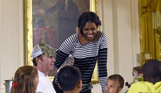 First lady Michelle Obama talks with school children as they eat lunch in the East Room of the White House following the annual fall harvest of the White House Kitchen Garden in Washington, Tuesday, Oct. 14, 2014. Chef Geoff Tracy second from left, sits at the table. In celebration of Farm to School Month, the Obama invited students from Arizona, California, and Ohio to participate in the fall harvest. These schools were selected because they are participating in farm to school programs that incorporate fresh, local food into their school meals, and they teach students about healthy eating through school gardens and nutrition education.(AP Photo/Susan Walsh)