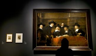 A woman looks at Rembrandt's painting The Sampling Officials of the Amsterdam Drapers' Guild, known as 'The Syndics', 1662 during a media event at The National Gallery in London, Tuesday, Oct. 14, 2014. The National Gallery will be holding an exhibition entitled 'Rembrant: The Late Works' which runs from Oct. 15 until Jan. 18, 2015. (AP Photo/Kirsty Wigglesworth)