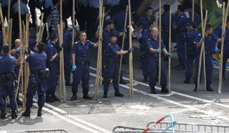 Police officers remove the bamboo barriers that protesters set up to block off main roads in Central district in Hong Kong Tuesday, Oct. 14, 2014. Hong Kong police cleared barricades from pro-democracy protest zones that have choked off traffic in key business districts for more than two weeks, signaling authorities' growing impatience with the student-led activists. (AP Photo/Kin Cheung)