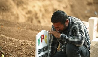 FILE - In this Saturday, Oct. 11, 2014 file photo, Kurdish Ali Mehmud mourns at the grave of his brother Seydo Mehmud 'Curo', a Kurdish fighter, who was killed in the fighting with the militants of the Islamic State group in Kobani, Syria, and was buried at a cemetery in Suruc, Turkey. No one contests that the U.S.-led coalition has conducted more than 40 airstrikes against the militants besieging Kobani, nor that Turkey has granted refuge to more than 200,000 people who have flooded across the border to escape the offensive. But Kurds say that both countries - and the international community in general - should be doing more to help save Kobani from the fanatical militants who have massacred and beheaded their enemies across Syria and Iraq. (AP Photo/Lefteris Pitarakis, File)