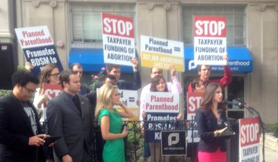 Outside the Planned Parenthood offices on 16th Street Northwest, representatives of pro-life groups, including Lila Rose, founder of Live Action [in pink skirt and black jacket], protest taxpayer support for the giant reproductive health services organization. (Photo by The Washington Times) ** FILE **