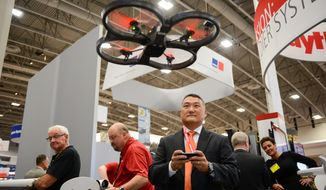Mission Manager Brian Stites with Ratheon, flies a hobbyist's AR Drone 2.0 to demonstrate the company's electronic armor, or anti-tamper system software they have developed to protect against hacking into military systems, during the 2014 Association of the United States Army's Annual Meeting and Exposition held at the Washington Convention Center, Washington, D.C., Tuesday, October 14, 2014. The software prevents tampering, and injection of malware into man and unmanned avionics and maritime, weapon and defense systems. (Andrew Harnik/The Washington Times)