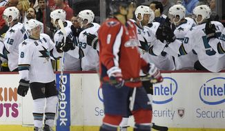 San Jose Sharks center Joe Pavelski (8) celebrates his goal with teammates on the bench as Washington Capitals left wing Alex Ovechkin, foreground, skates by during the second period of an NHL hockey game, Tuesday, Oct. 14, 2014, in Washington. The Sharks won 6-5 in a shootout. (AP Photo/Nick Wass)