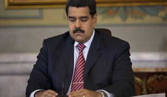 Venezuela's President Nicolas Maduro closes his eyes for a few moments before starting a press conference at Miraflores presidential palace in Caracas, Venezuela, Wednesday, Oct. 15, 2014. (AP Photo/Ariana Cubillos)