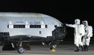 In this Dec. 3, 2010, file image provided by the Vandenberg Air Force Base shows technicians examining the X-37B unmanned space plane shortly after landing at Vandenberg Air Force Base, Calif.  (AP Photo/Vandenberg Air Force Base) ** FILE **