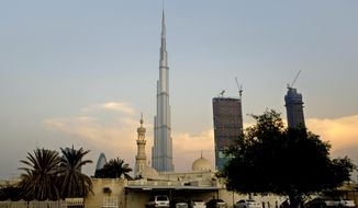 This Sunday, Aug. 7, 2011, file photo shows the World's tallest tower, Burj Khalifa, in the background as children play next to a mosque in Dubai, United Arab Emirates. (AP Photo/Kamran Jebreili, File)