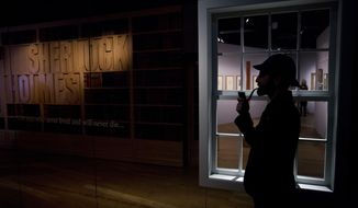"Curator Timothy Long is silhouetted as he poses for photographers with a Sherlock Holmes style pipe and deerstalker hat beside an internal window forming part of the exhibition ""Sherlock Holmes:  The Man Who Never Lived and Will Never Die"" at the Museum of London in London, Thursday, Oct. 16, 2014. The exhibition, which opens to the public on Friday, is the largest on the fictional detective created by Scottish author Sir Arthur Conan Doyle to be held in the UK for 60 years  (AP Photo/Matt Dunham)"