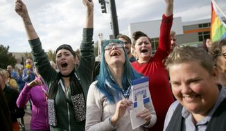 Well-wishers yell encouragement to same sex couples, including Karen McMillan, right, make their way out of the Ada County Courthouse after they received their marriage license, Wednesday, Oct. 15, 2014, in Boise, Idaho. (AP Photo/The Idaho Statesman, Kyle Green)  LOCAL TELEVISION OUT (KTVB 7); MANDATORY CREDIT