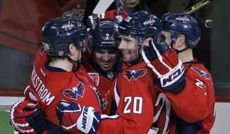 Washington Capitals center Nicklas Backstrom, left, from Sweden, celebrates his goal with defenseman Matt Niskanen (2), right wing Troy Brouwer (20), and others in the third period of an NHL hockey game against the New Jersey Devils, Thursday, Oct. 16, 2014, in Washington. The Capitals won 6-2. (AP Photo/Alex Brandon)