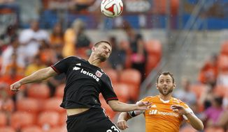Houston Dynamo midfielder Brad Davis (11) goes up for a header against D.C. United midfielder/defender Perry Kitchen (23) during the first half of an MLS soccer match at BBVA Compass Stadium, Sunday, Oct. 12, 2014, in Houston. (AP Photo/Houston Chronicle, Karen Warren)