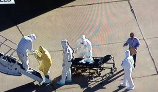 This TV screen shot shows a man with a clipboard on the tarmac with an Ebola patient.