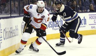 Calgary Flames' Curtis Glencross (20) stays in front of Columbus Blue Jaqckets' Fedor Tyutin (51), of Russia, during the second period of an NHL hockey game, Friday, Oct. 17, 2014, in Columbus, Ohio. The Blue Jackets won 3-2. (AP Photo/Mike Munden)