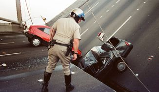 In this Oct. 17, 1989, file photo, a California Highway Patrol officer checks the damage to cars that fell when the upper deck of the Bay Bridge collapsed onto the lower deck after the Loma Prieta earthquake in San Francisco. (AP Photo/George Nikitin, File)