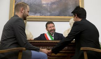 Rome's Mayor Ignazio Marino, center, smiles as he registers the gay marriage between Jonathon Dominic Spada, left, and Fabrizio Maffeo, in Rome, Saturday, Oct. 18, 2014. Marino has registered 16 gay marriages entered abroad in open defiance of Italy's Interior Ministry. Gay marriage is illegal in Italy. Interior Minister Angelino Alfano recently sent a notice to local prefects saying any registrations of gay marriages celebrated abroad would be voided. (AP Photo/Andrew Medichini)