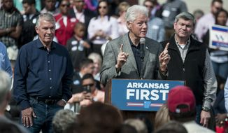 Democratic candidates James Lee Witt, left, and Mike Ross, right, watch former President Bill Clinton speak to the crowd during a rally at the train depot in his hometown of Hope, Ark. Saturday, Oct, 18, 2014. Clinton praised all of the democratic candidates up for election and touched on topics such as the Ebola and healthcare.  (AP Photo/Texarkana Gazette, Jerry Habraken)