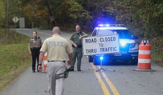 Albemarle County police block off a section of Old Lynchburg Road south of Red Hill Road Saturday, OCT. 18, 2014, in Albemarle County, Va. (AP Photo/The Daily Progress, Andrew Shurtleff)