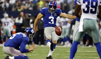 New York Giants punter Steve Weatherford (5) holds as kicker Josh Brown (3) kicks the extra point as Dallas Cowboys cornerback Brandon Carr (39) watches during the first half of an NFL football game, Sunday, Oct. 19, 2014, in Arlington, Texas. (AP Photo/LM Otero)