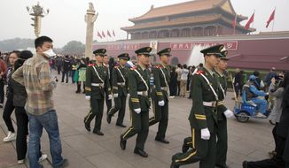 In this photo taken Saturday, Oct. 11, 2014, Chinese paramilitary policemen march across Tiananmen Gate in Beijing. The most important meeting of the year for the 205 members of China's ruling Communist Party's Central Committee, beginning Monday, Oct 20, 2014, will focus on how to rule the country in accordance with law. That has fed hopes that the party might move to respect the letter of the constitution, but some legal experts and political analysts say the country's leaders are intent on expanding power, not limiting it. (AP Photo/Ng Han Guan)