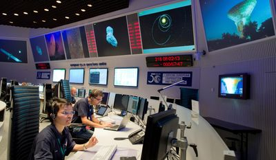 Experts watch their screens at the control center of the European Space Agency, ESA, in Darmstadt, Germany during a mission to land the first space probe on a comet. (AP Photo/dpa, Boris Roessler)