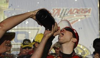 Brad Keselowski drinks champagne after winning the NASCAR Sprint Cup Series auto race at Talladega Superspeedway, Sunday, Oct. 19, 2014, in Talladega, Ala. (AP Photo/Rainier Ehrhardt)