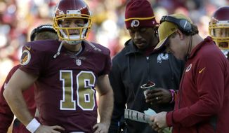 Washington Redskins quarterback Colt McCoy (16) stands with quarterback Robert Griffin III, center, and head coach Jay Gruden during a break in the action in the second half of an NFL football game against the Tennessee Titans, Sunday, Oct. 19, 2014, in Landover, Md. (AP Photo/Pablo Martinez Monsivais)