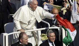 Pope Francis catches an Italian flag thrown by a pilgrim, at the end of the beatification ceremony of Pope Paul VI, and a mass celebrated for the closing of of a two-week synod on family issues, in Saint Peter's Square at the Vatican, Sunday, Oct. 19, 2014. Pope Francis on Sunday beatified Pope Paul VI, concluding the remarkable meeting of bishops debating family issues that drew parallels to the tumultuous reforms of the Second Vatican Council which Paul oversaw and implemented. (AP Photo/Gregorio Borgia)