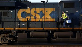 In this March 22, 2014, file photo, a crew member walks on a CSX freight train engine in Brunswick, Md. (AP Photo/Patrick Semansky, File)