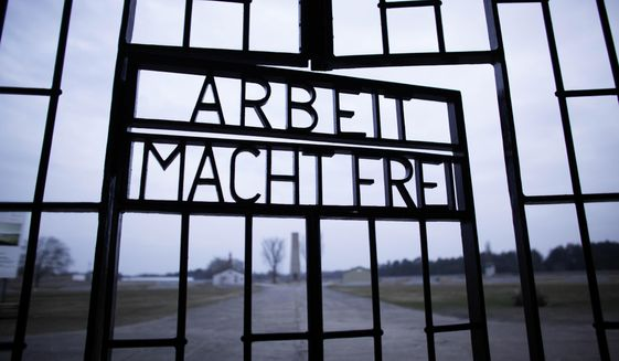 This Jan. 27, 2012, file photo shows the words 'Arbeit Macht Frei' (Work Sets You Free) at the main entrance of the Sachsenhausen Nazi concentration camp on the international Holocaust remembrance day in Oranienburg, Germany.  (AP Photo/Markus Schreiber, File)