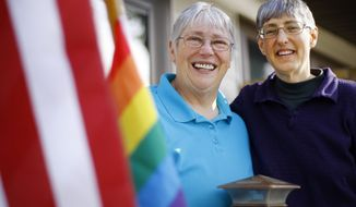 Paula McDaniel and Donna West pose with their American and rainbow flags on their front porch on Friday, Oct. 17, 2014, in Casper, Wyo. West brought out the rainbow flag after hearing the news that Wyoming's ban on gay marriage has been struck down. Gay couples are expected to be able to marry in Wyoming beginning Tuesday morning, Oct. 21, 2014. (AP Photo, Casper Star-Tribune, Dan Cepeda)