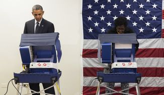 President Barack Obama, left, cast a ballot for the 2014 midterm elections at the Dr. Martin Luther King Community Service Center while participating in early voting on Monday, Oct. 20, 2014, in Chicago. Obama took a break from campaigning for Gov. Pat Quinn, D-Ill., to cast an early ballot for the election. (AP Photo/Evan Vucci)