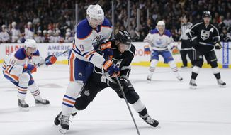 Edmonton Oilers' Justin Schultz (19) and Los Angeles Kings' Slava Voynov (26), of Russia, compete for the puck during the first period of an NHL hockey game Tuesday, Oct. 14, 2014, in Los Angeles.(AP Photo/Jae C. Hong)