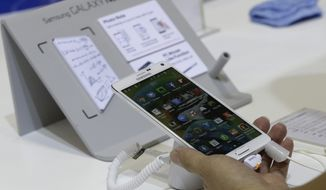 In this Tuesday, Oct. 14, 2014, file photo, a visitor tries out a Samsung Electronics Co.'s Galaxy Note 4 smartphone during the 2014 Korea Electronics Show in Goyang, South Korea. (AP Photo/Ahn Young-joon, File)