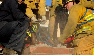 In this Sunday, Oct. 19, 2014 photo provided by the Ventura County Fire Department, firefighters work to free Genoveva Nunez-Figueroa, 30, from a chimney after she became stuck trying to enter a home in Thousand Oaks, Calif. Firefighters had to chisel away much of the chimney and lubricate it with dish soap to free her. (AP Photo/Ventura County Fire Department)