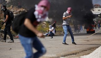 A Palestinian protester hurls stones towards Israel troops during clashes at a protest solidarity with demonstrators at al-Aqsa mosque in Jerusalem, outside the Ofer military prison, near the West Bank city of Ramallah, Tuesday, Oct. 21, 2014. (AP Photo/Majdi Mohammed) ** FILE **
