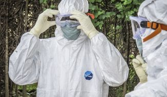 Health workers wear protective gears before entering the house of a person suspected to have died of Ebola virus in Port loko Community situated on the outskirts of Freetown, Sierra Leone, Tuesday, Oct. 21, 2014. After emerging months ago in eastern Sierra Leone, Ebola is now hitting the western edges of the country where the capital is located with dozens of people falling sick each day, the government said Tuesday. So many people are dying that removing bodies is reportedly a problem. (AP Photo/Michael Duff)