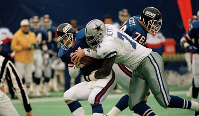 New York Giants quarterback Phil Simms (11) is sacked by Dallas Cowboys Jim Jeffcoat during the fourth quarter at Giants Stadium, Jan. 2, 1994. (AP Photo/Bill Kostroun)