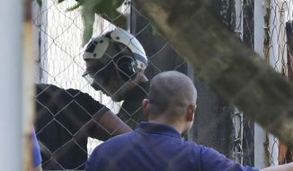 U.S. Marines Pfc Joseph Scott Pemberton, a suspect in the gruesome killing of a transgender Filipino woman, wears a helmet as he arrives inside the compound of the Camp Aguinaldo military headquarters in suburban Quezon city, north of Manila, Philippines on Wednesday, Oct. 22, 2014. The Philippine military chief says Pemberton has been flown to the main Philippine military camp in the capital, easing a looming irritant with Washington over his custody, officials said. (AP Photo/Aaron Favila)