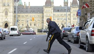 Police secure an area around Parliament Hill in Ottawa on Wednesday Oct. 22, 2014.  A soldier standing guard at the National War Memorial was shot by an unknown gunman and people reported hearing gunfire inside the halls of Parliament. Prime Minister Stephen Harper was rushed away from Parliament Hill to an undisclosed location, according to officials. (AP Photo/The Canadian Press, Adrian Wyld)