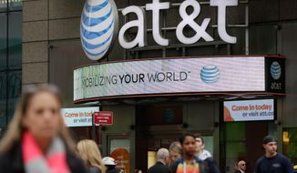 In this Tuesday, Oct. 21, 2014 photo, people pass an AT&T store, in New York's Times Square. AT&T reports quarterly financial results on Wednesday, Oct. 22, 2014. (AP Photo/Richard Drew)