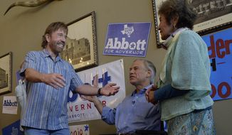 Republican gubernatorial candidate Greg Abbott, middle, introduces actor Chuck Norris to his mother-in-law, Mary Lucy Phalen, during a campaign event at the Casa Rio restaurant in San Antonio, Texas, on Wednesday, Oct. 22, 2014. (AP Photo/San Antonio Express-News, Billy Calzada)