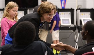 Democratic candidate for U.S. Senate Michelle Nunn, center, with her daughter Elizabeth, greets early voters after she cast a ballot at Fulton County's Adamsville Recreation Center in Atlanta in this Oct. 15, 2014, file photo. (AP Photo/David Tulis, File)