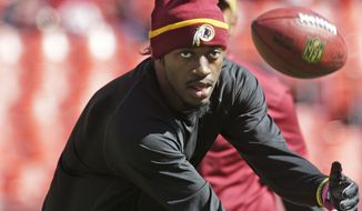 Washington Redskins quarterback Robert Griffin III catches a football during pregame activities before a NFL football game against the Tennessee Titians, Sunday, Oct. 19, 2014. at Fedex Field in Landover, MD. (AP Photo/Pablo Martinez Monsivais)