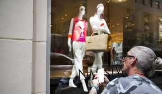 Ray Souders, lead stylist for Neiman Marcus, adds window decals to a summer sale display on a shop window of the luxury retailer's flagship store, on S. Ervay Street in downtown Dallas on May 29, 2014. (AP Photo/The Dallas Morning News, Brittany Sowacke) ** FILE **