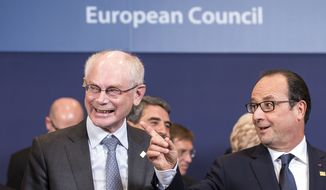 French President Francois Hollande, right, speaks with European Council President Herman Van Rompuy during a group photo at an EU summit in Brussels, on Thursday, Oct. 23, 2014. EU leaders gathered Thursday for a two-day summit in which they will discuss Ebola, climate change and the economy. (AP Photo/Geert Vanden Wijngaert)